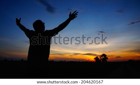 Silhouette of man with arms wide open during sunset