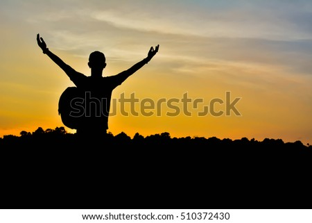 Silhouette of man with backpack open hand on the sky sunset background ,alone and wait to travel