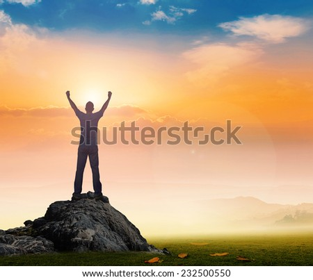 Silhouette of man with hand raised to beautiful autumn sunset background. World Mental Health Day Thanksgiving Christmas Forgiveness Mercy Repentance Reconcile Glorify Evangelical Humanitarian concept - stock photo