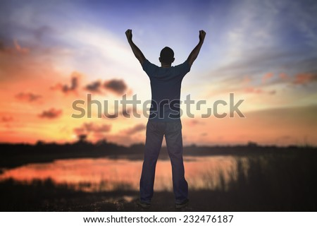 Silhouette of man with hands raised to beautiful autumn sunset background. A disabled man standing up. Cure Recovery Medical Miracle Hope Insurance Hallelujah Human Rights Day Sick Memorial concept.
