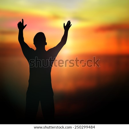 Silhouette of man with hands raised to beautiful sunset background.