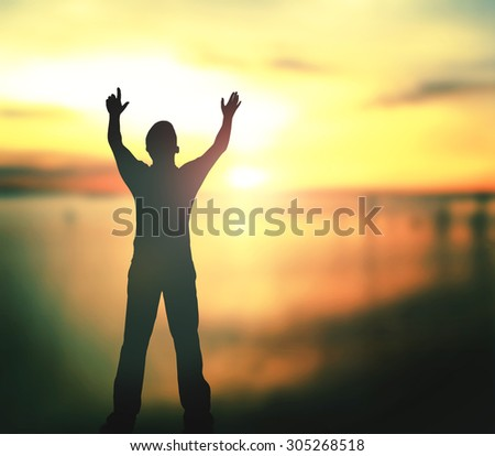 Silhouette of man with hands raised to beautiful sunset background. World Mental Health Day concept. - stock photo