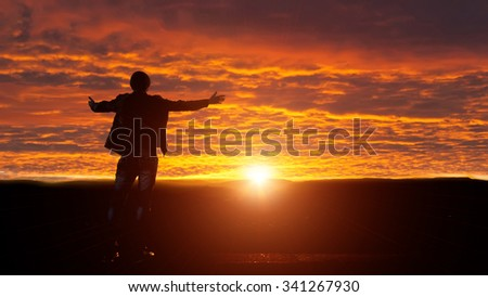 Silhouette of man with his arms raised. A ray of sunshine in the mountains.