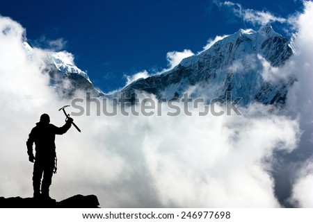 Silhouette of man with ice axe in hand and mountains with clouds - Mount Thamserku and Mount Kangtega - Nepal - stock photo