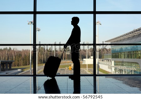 silhouette of man with luggage standing near window in airport side view