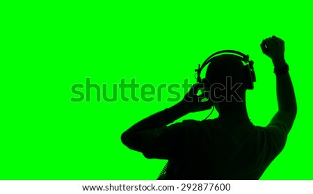 Silhouette of man with raised hand dancing as disc jockey.Green background - stock photo