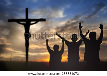 Silhouette of man with raised hands over blur cross concept for religion, worship, prayer and praise.