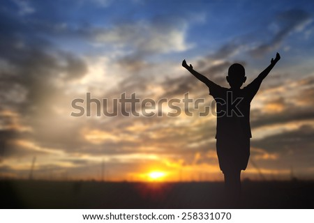 Silhouette of man with raised hands over blur nature concept for religion, worship, prayer and praise. - stock photo