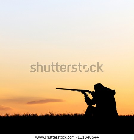 Silhouette of man with rifle aiming the hunt during a hunting party - stock photo
