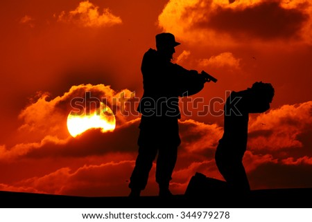 Silhouette of man with rifle pointed at victim's back