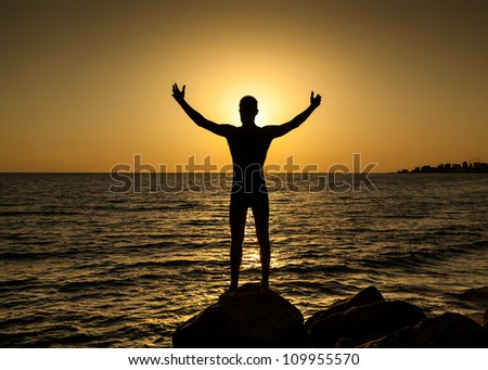 Silhouette of man with their hands in the sunset on the ocean - stock photo