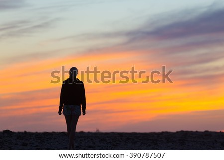 Silhouette of meditative, sensual blonde woman watching sunset at the beach.