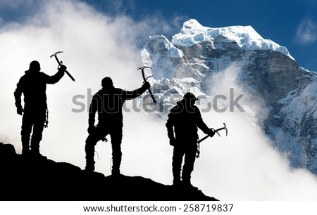 Silhouette of men with ice axe in hand and mountains with clouds - Mount Thamserku and Mount Kangtega - Nepal