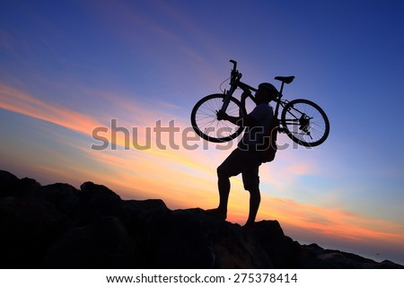 Silhouette of mighty man in action lifting bike on his shoulder on rock mountain with sunrise twilight background. Symbol of relax, success and touring. - stock photo