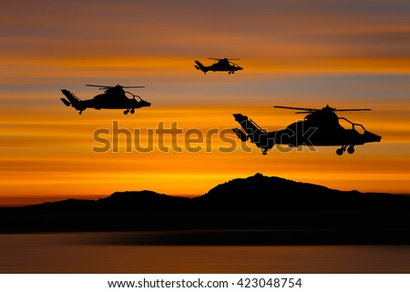 Silhouette of military Helicopters with mountains and sunset background