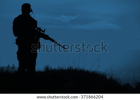 Silhouette of military sniper with sniper gun at night. shot, holding gun, colorful sky, background - stock photo