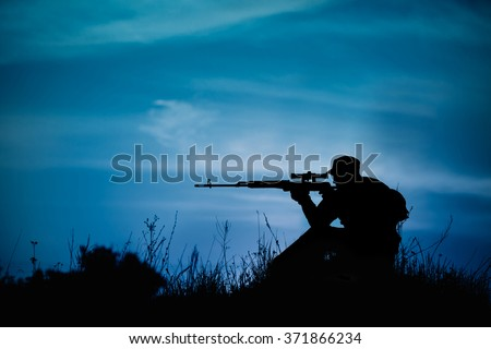 Silhouette of military sniper with weapons at night. shot, holding gun, blue colorful sky, background - stock photo