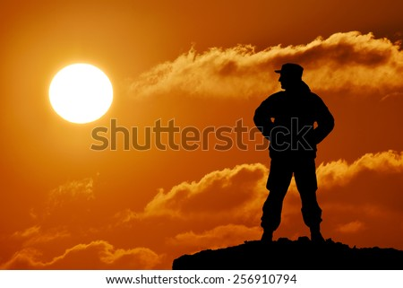 Silhouette of military soldier or officer with weapon at sunset. colorful sky, mountain, background, landscape