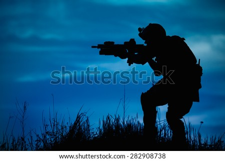 Silhouette of military soldier or officer with weapons at night. shot, holding gun, blue colorful sky, background - stock photo