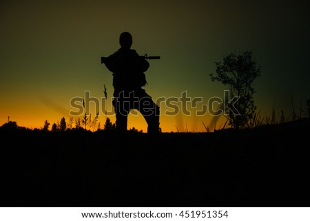 Silhouette of military soldier or officer with weapons at night. shot, holding gun, colorful sky, background - stock photo