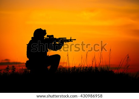 Silhouette of military soldier or officer with weapons. shot, holding gun, colorful sky, background. war and military concept.