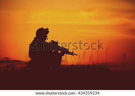 Silhouette of military soldier or officer with weapons. shot, holding gun, colorful sky, background. war and military concept. - stock photo