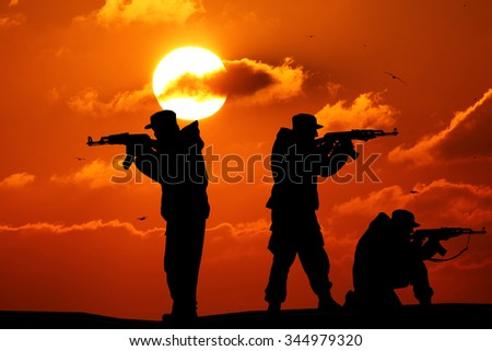 Silhouette of military three soldiers or officer with weapons at sunset. shot, holding gun, colorful sky, mountain, background, team