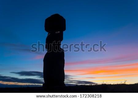 Silhouette of moai against a colorful sky at sunset at Ahu Tahai, Easter Island (Rapa Nui), Chile - stock photo