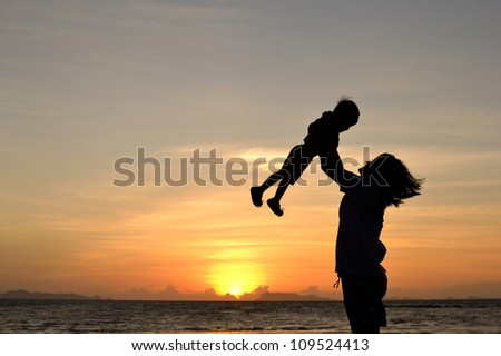 silhouette of mommy and small girl on the beach at dusk.