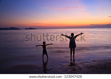 Silhouette of mother  and a child at the coast - stock photo