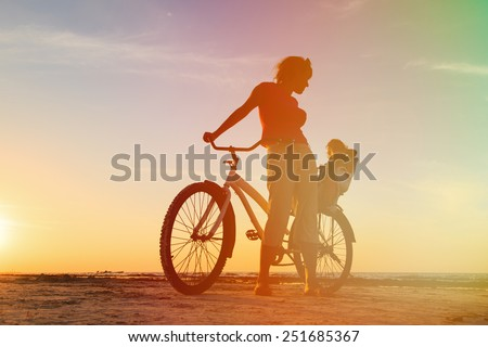 Silhouette of mother and baby biking at sunset