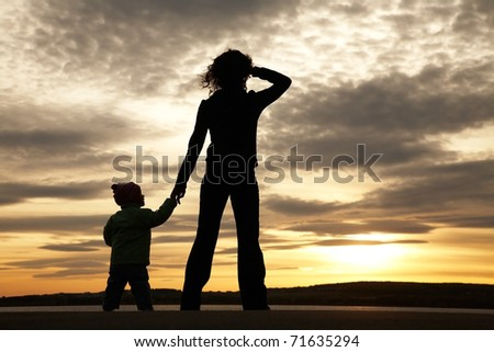 Silhouette of mother and baby looking away into the sunset and water - stock photo