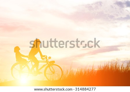 Silhouette of mother and daughter biking at sunset happy time