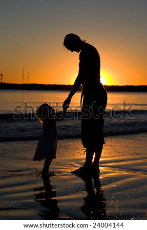 Silhouette of mother and daughter on the beach at sunset.  Backlit by the setting sun.