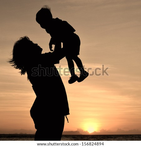 silhouette of mother and small girl on the beach at dusk.