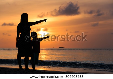 silhouette of mother and son at sunset beach, pointing at the sun