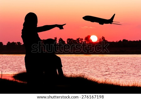 silhouette of mother hugging her son use hand point airplane on the sky at sunset - stock photo