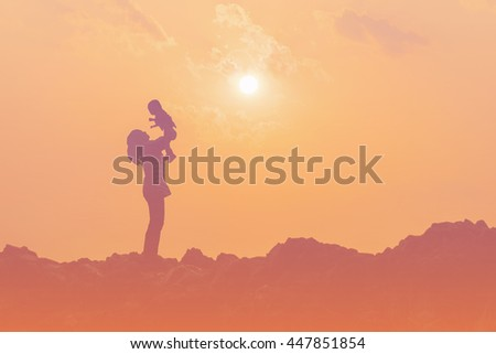 Silhouette of mother playing with baby on sunset over the silhouette mountain hills retro filter
