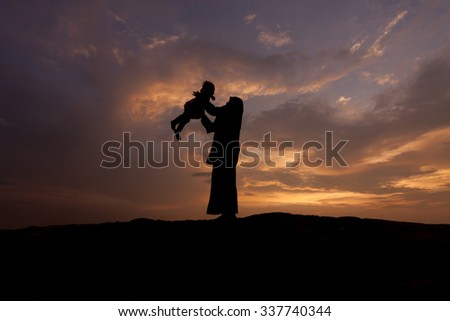 Silhouette of mother which turns the child against a sunset