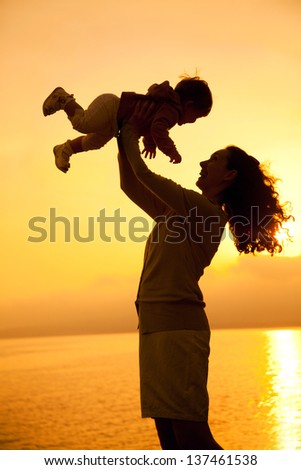 Silhouette of mother which turns the child against a sunset and water