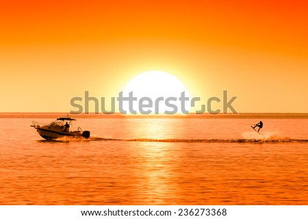 silhouette of motor boat and wakeboarder at sunset performing crazy trick   - stock photo