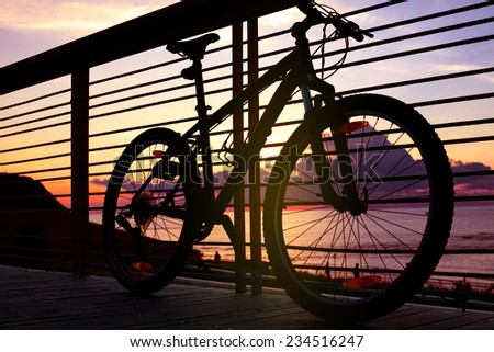 silhouette of mountain bike near the railing in front of the ocean at sunset