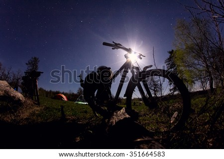 Silhouette of mountain bike night with moon and stars