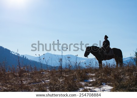 Silhouette of mountain rider on a horse. - stock photo