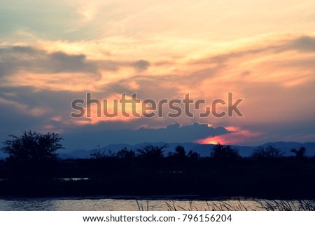 Silhouette of  mountain with beautiful blue sky and dark cloud at sunset ,  Horizon began to turn orange with gold color in tropical areas , Thailand