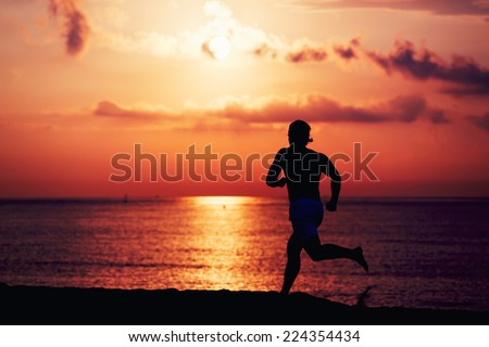 Silhouette of muscular build athlete running fast a log the beach, runner in action jogging against colorful sunrise over the sea