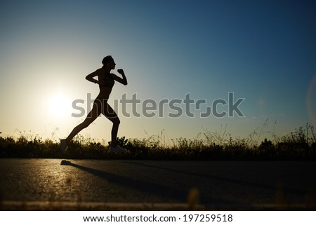 Silhouette of muscular women running on the road at sunset