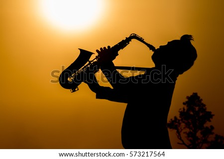 Silhouette of musician with saxophone sunset field