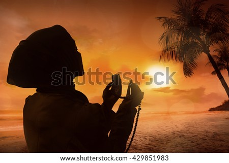 Silhouette of muslim woman praying on the beach
