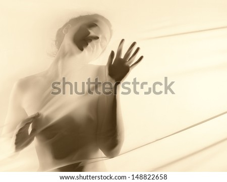 silhouette of naked girl touching the material  - stock photo
